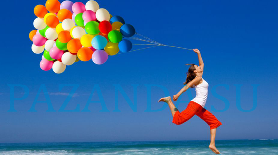 Beautiful and athletic girl running and jumping with colorful balloons on the beach